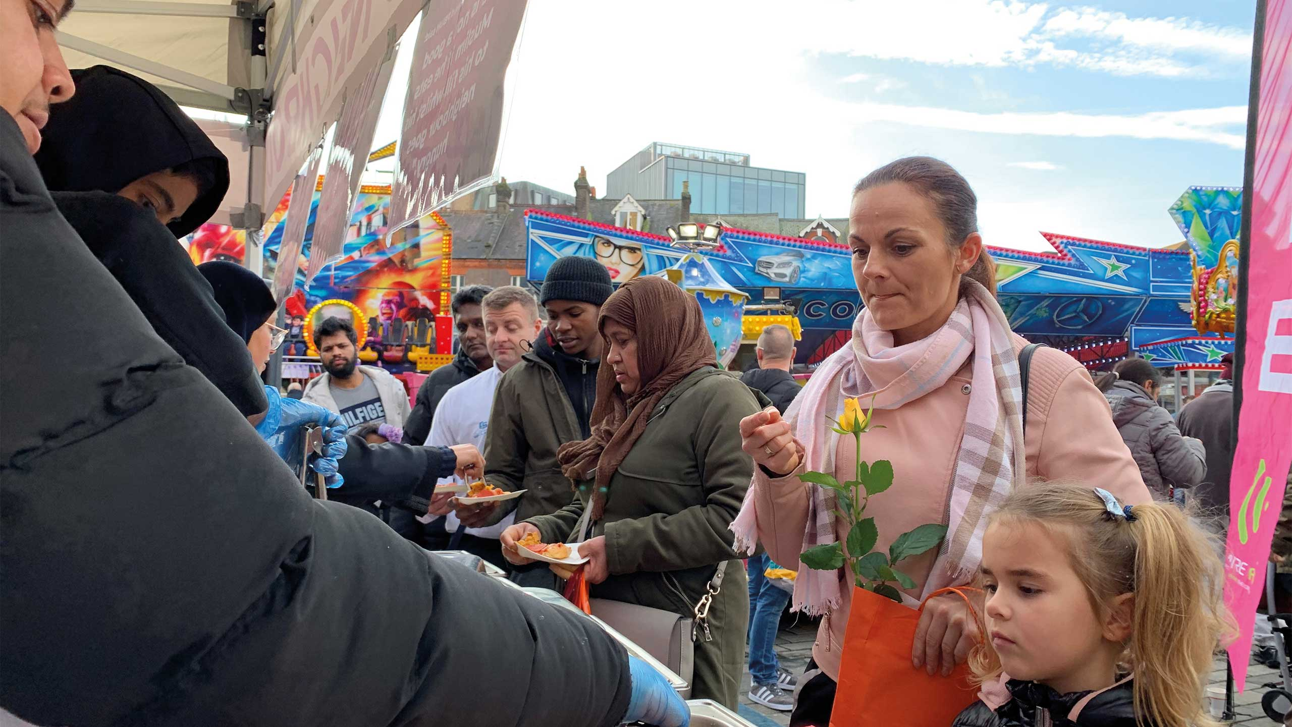 Image of line of people being served free food infront of rides at St. George's Square