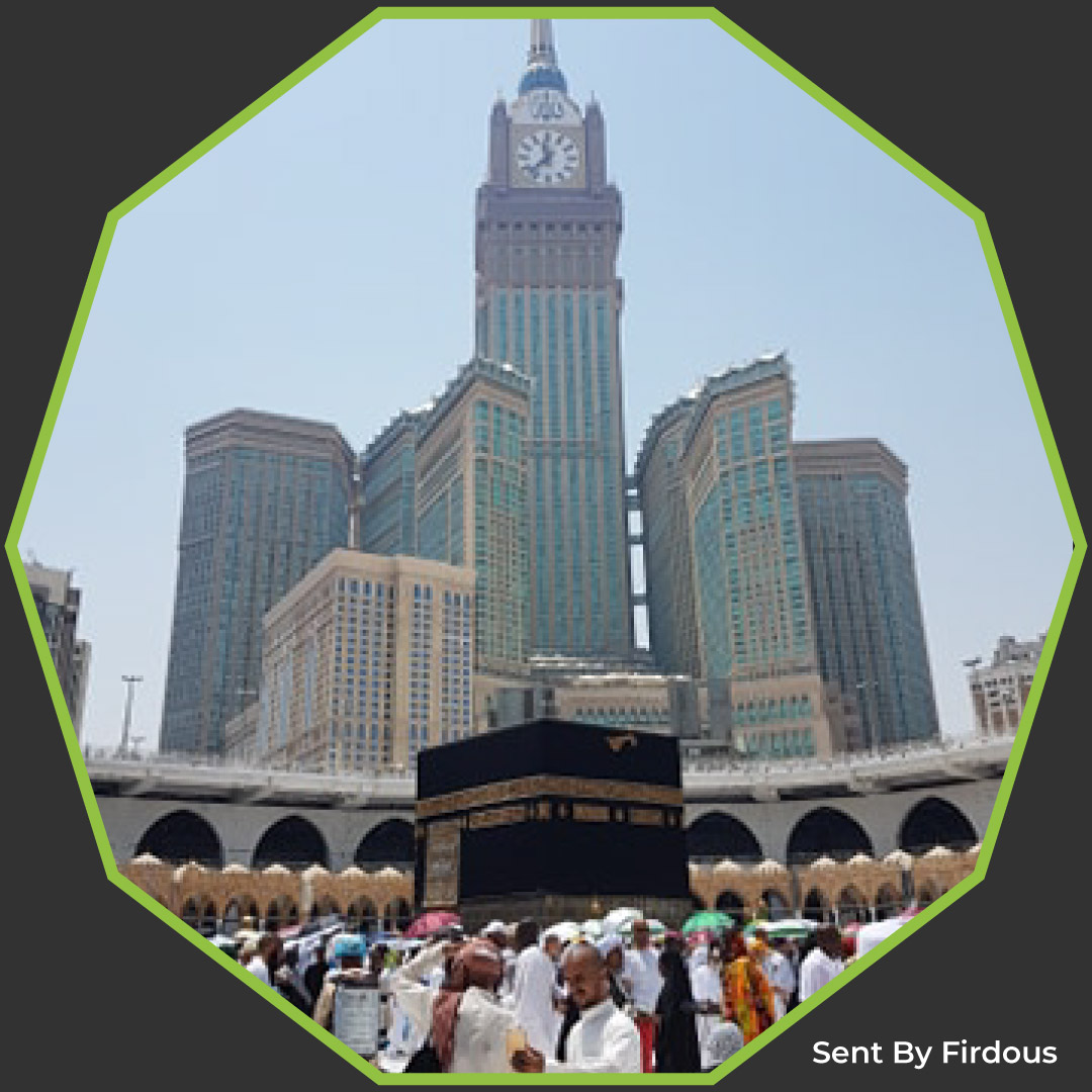 image of kabbah (cube buidling) with high rise building behind and clock tower