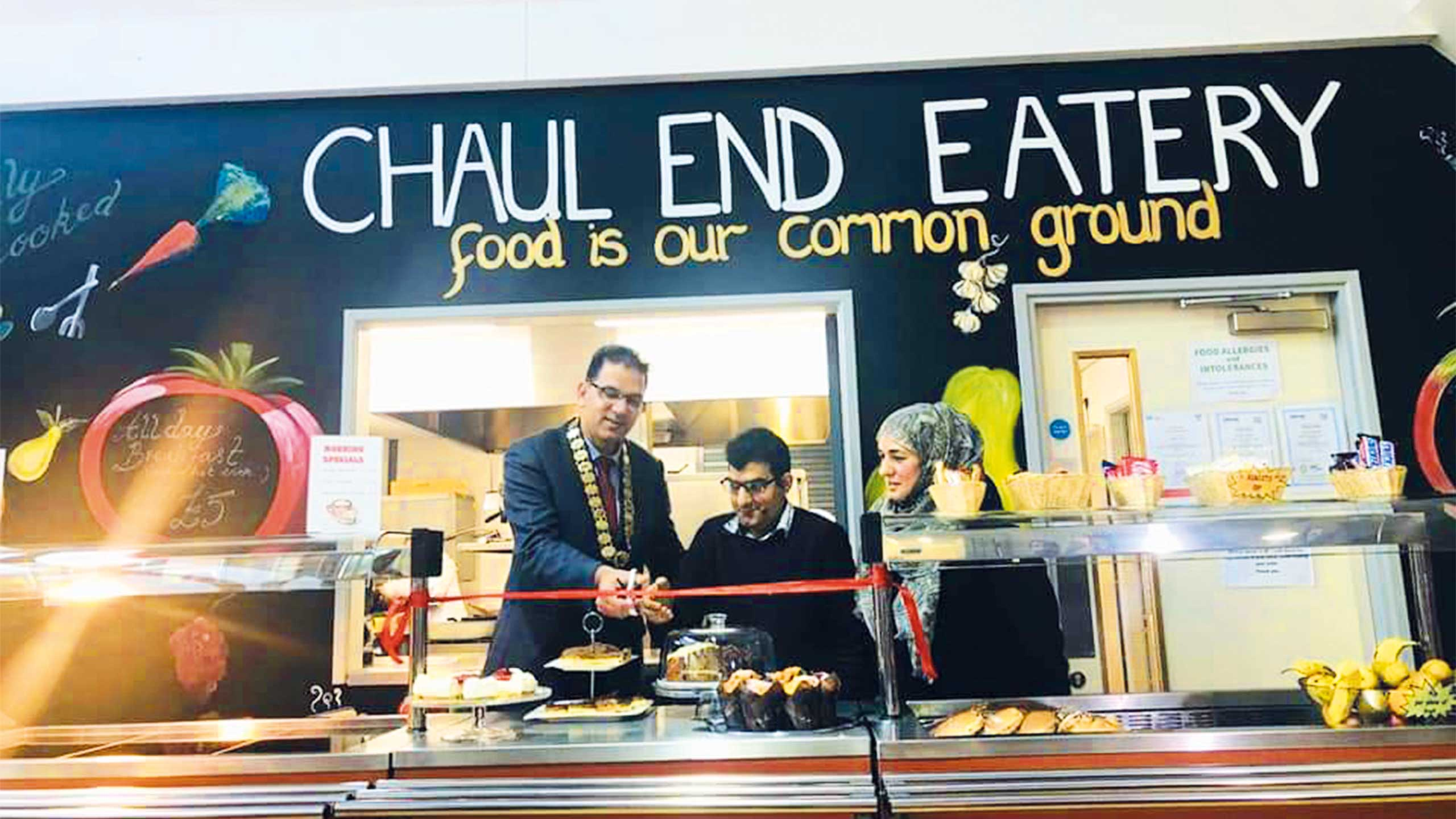 Mayor of Luton with manager of the chaul end eatery, Shigufta and one of the customers cutting the ribbon officially opening the Chaul End eatery infront of the serving table with food layed out including cakes.