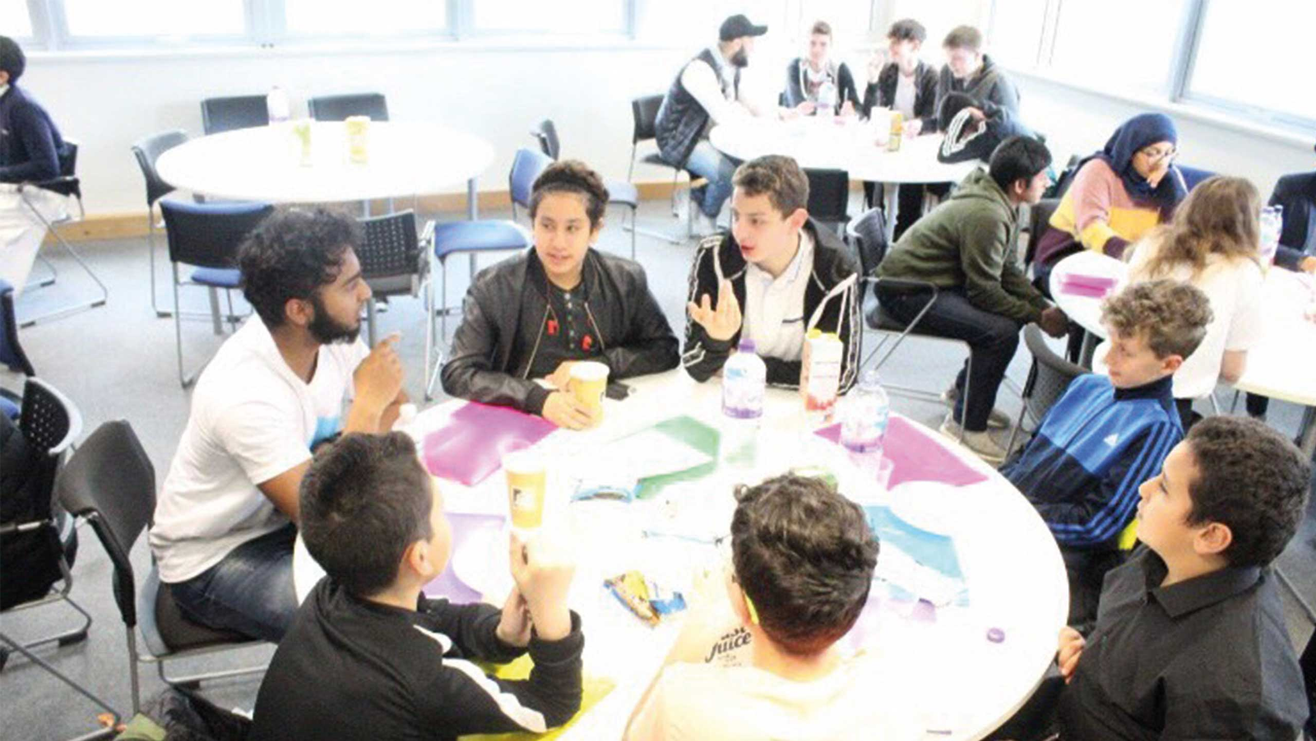 tables with young people sitting around discussing ideas for their dragons den style pitch