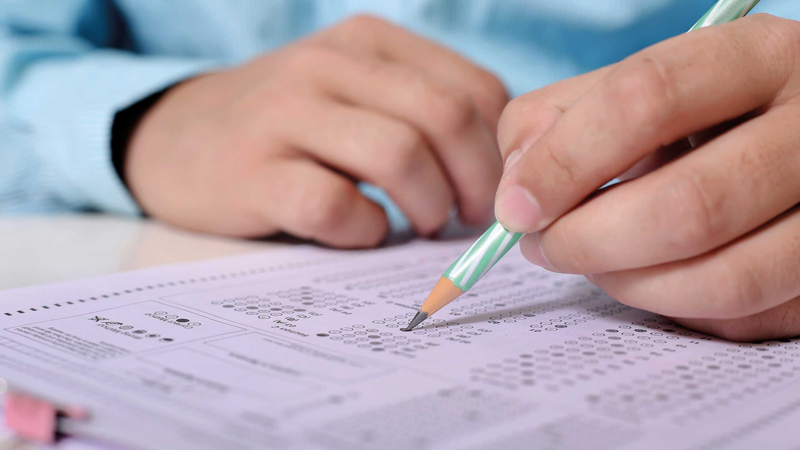 student filling exam paper with pencil