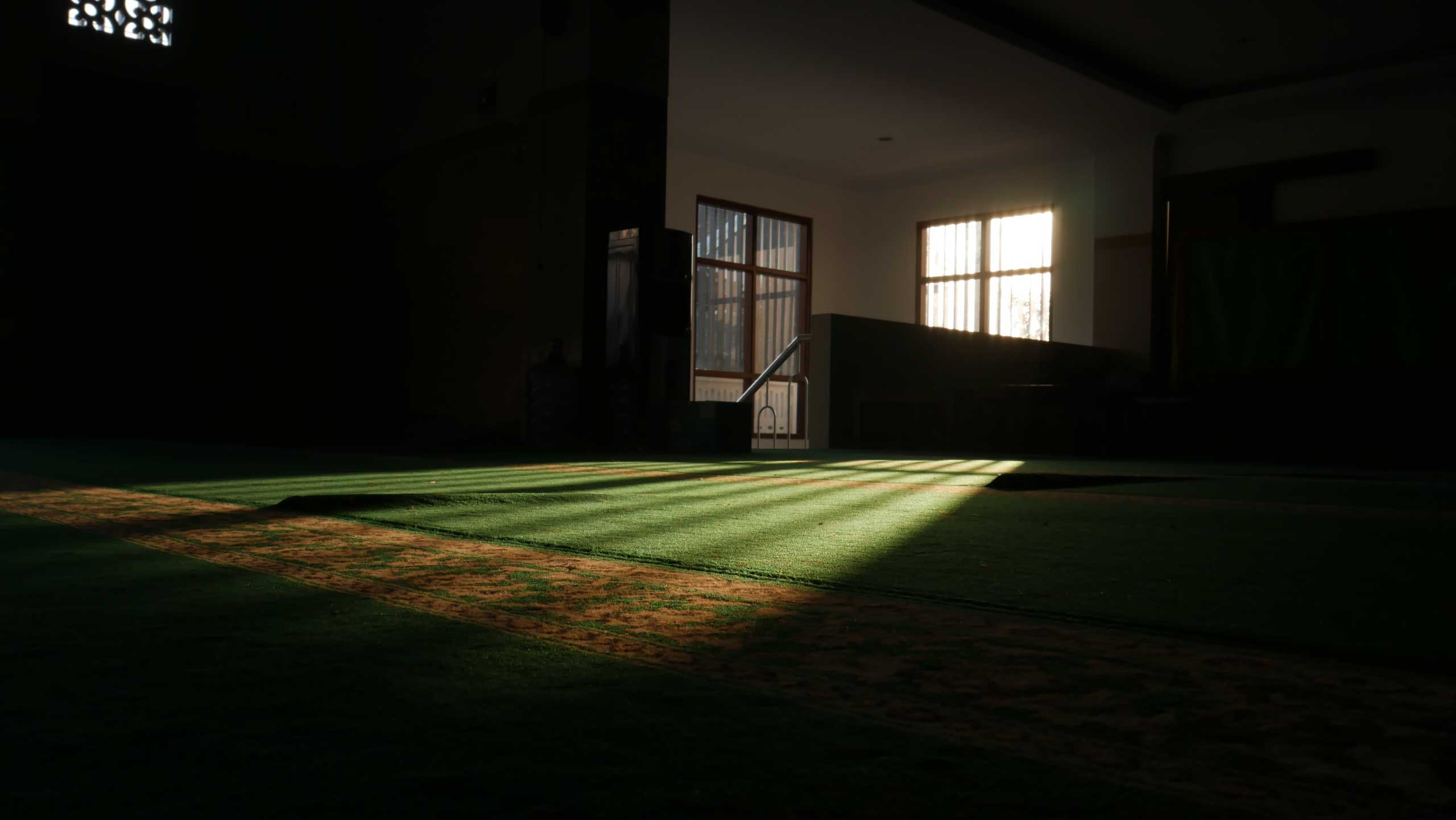 inside mosque with carpet and light coming through window