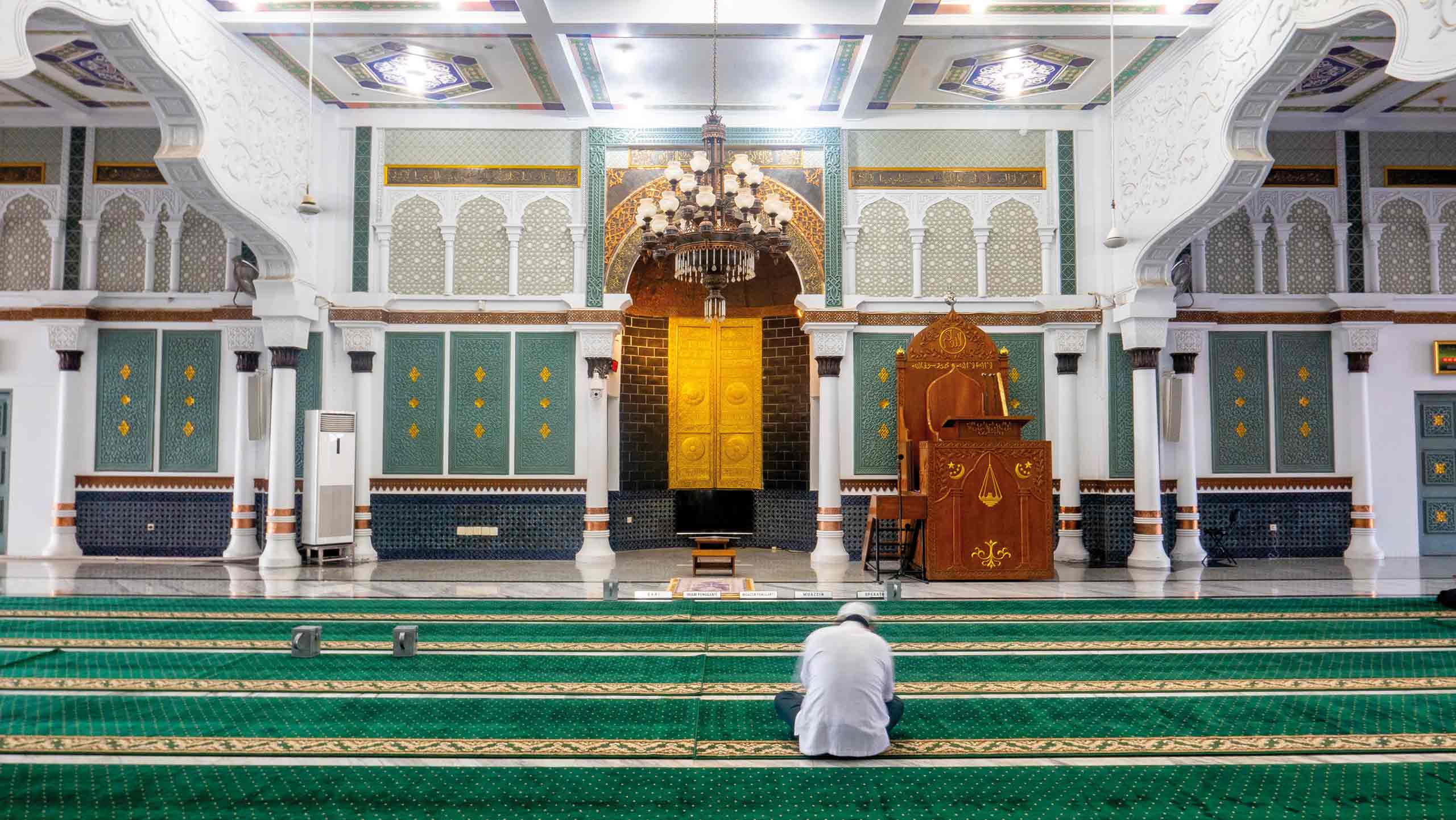 man sitting in empty mosque with decorative walls