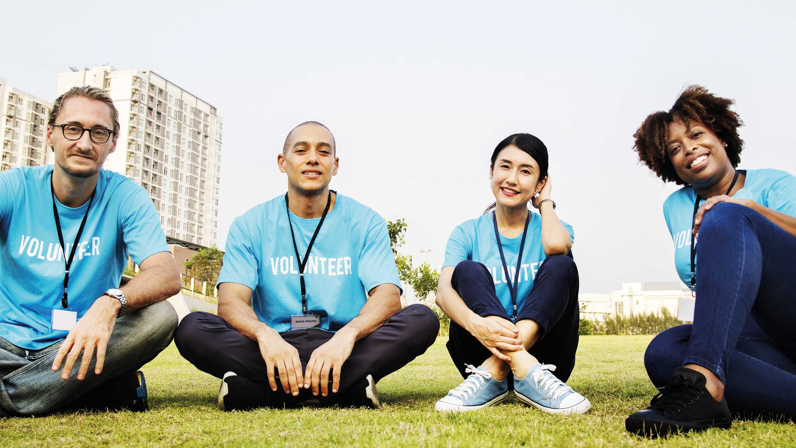 image of volunteers with matching t-shirts sat on some grass facing the camera