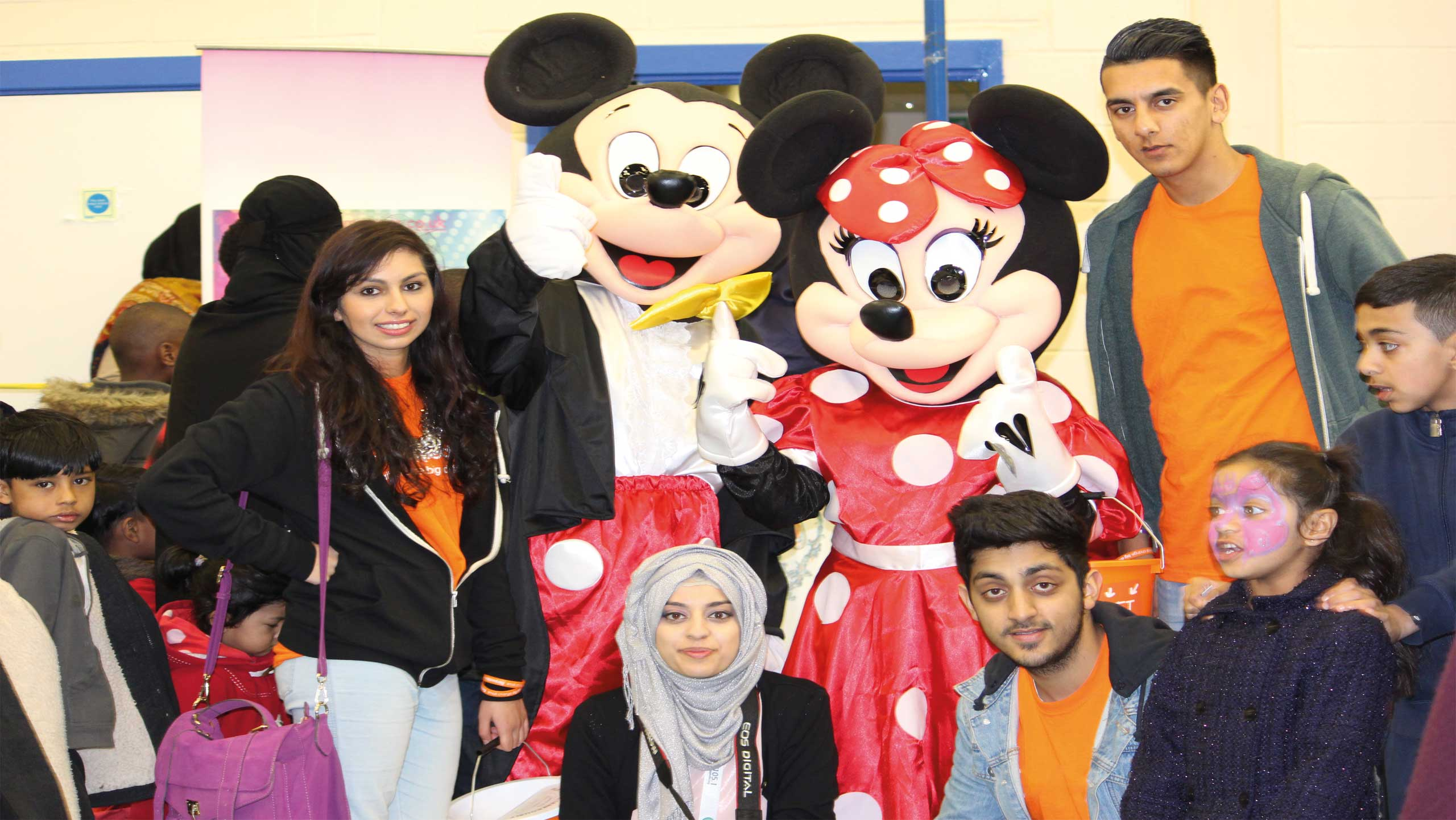 group of volunteers with mikey and mini mouse mascots at a previous family funday event