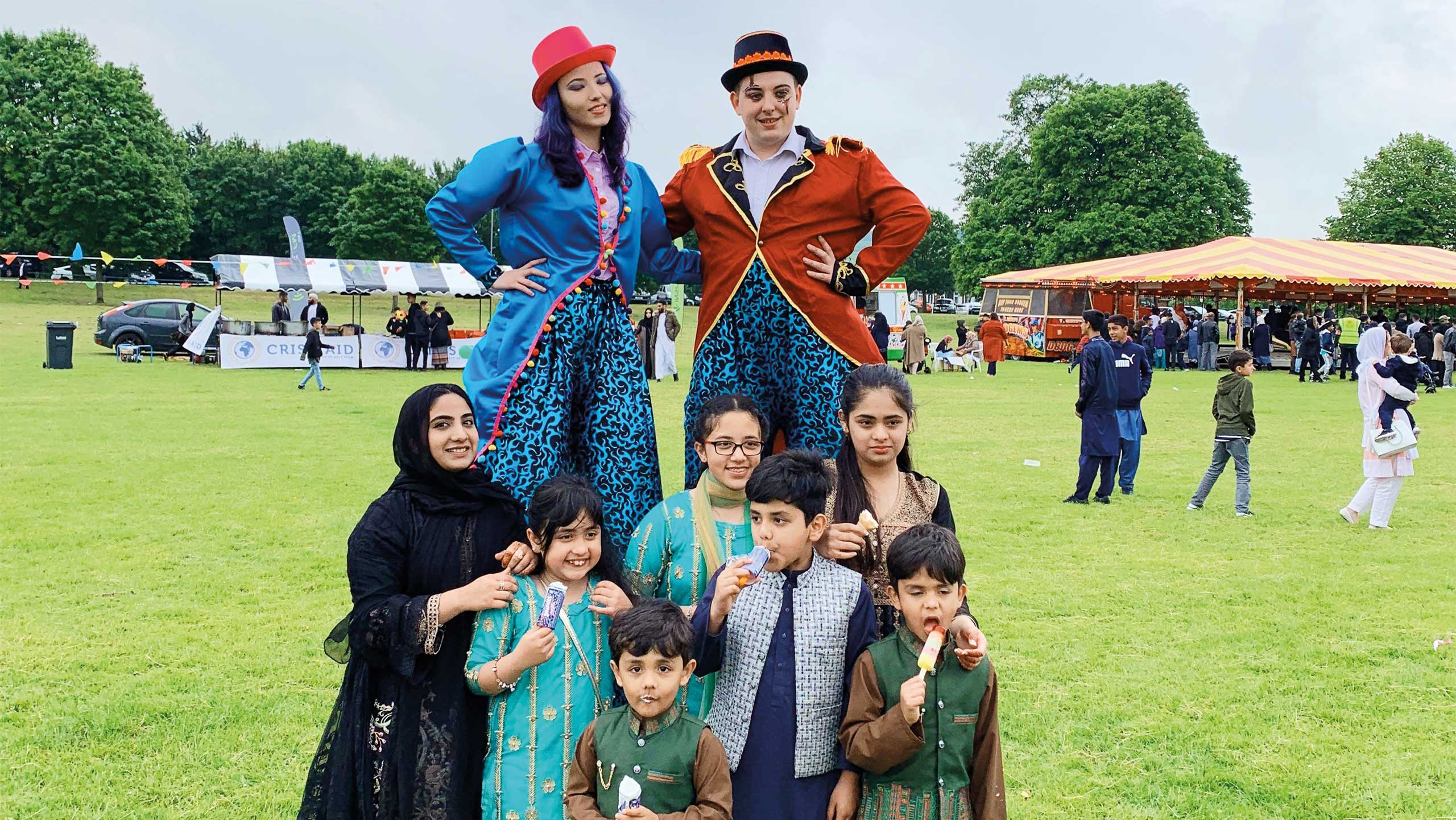 group photo at Inspire Eid with family in front of stilt walkers