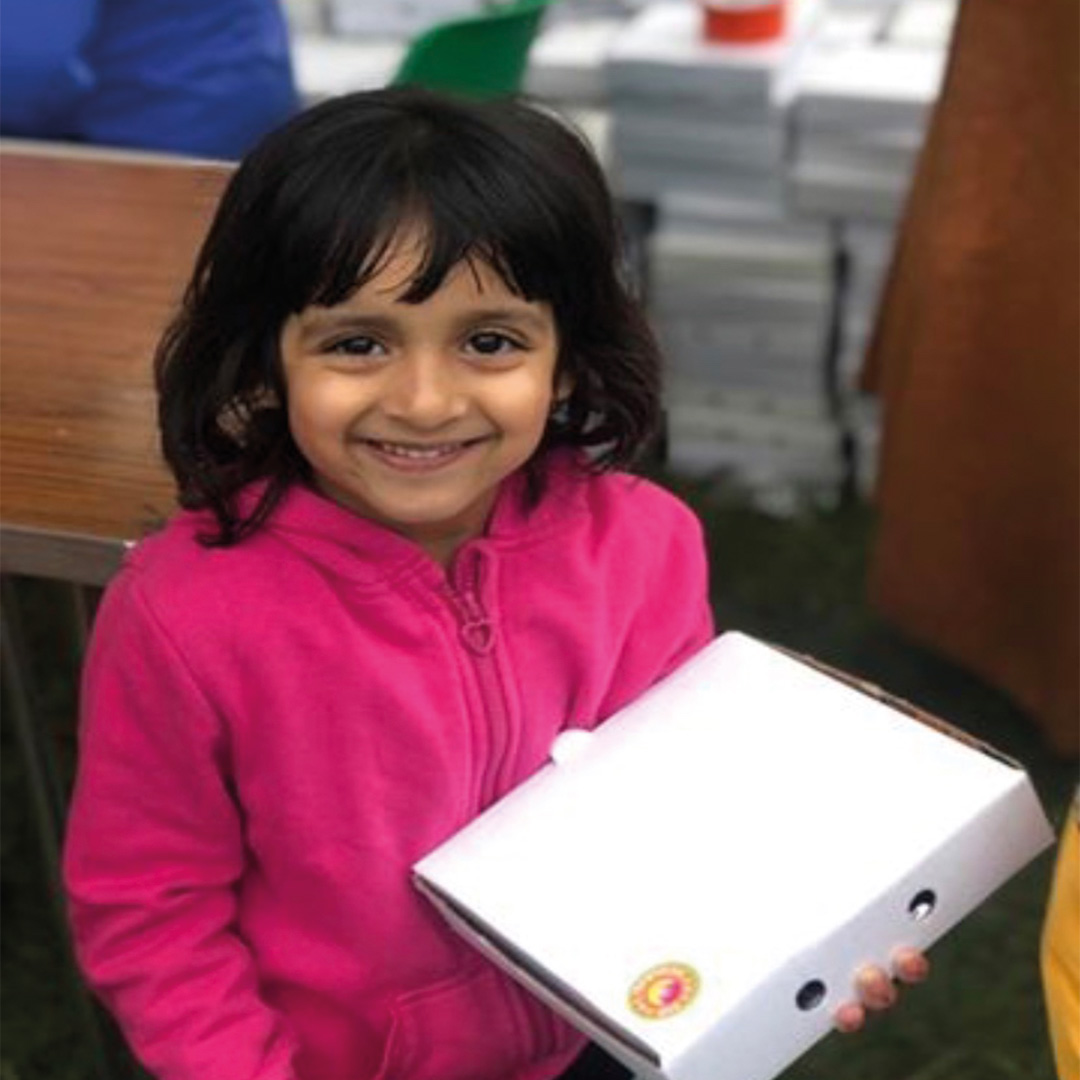 child with an eid gift box in her hand