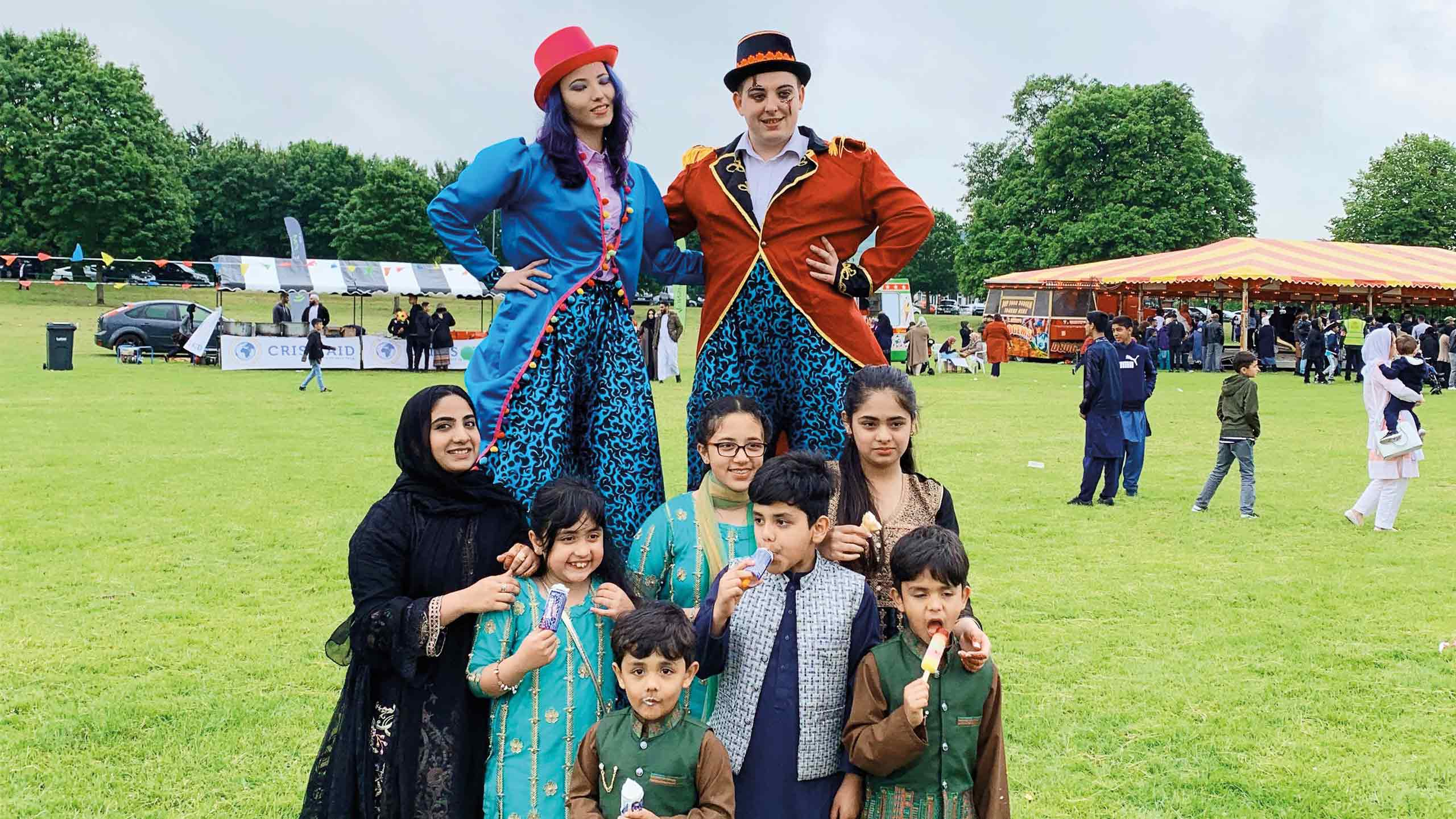 Family photo with two stilt walkers at the Inspire Eid event in Lewsey Park